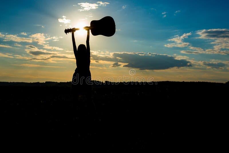 Silhouetvrouw het spelen gitaar in zonsondergang stock fotografie