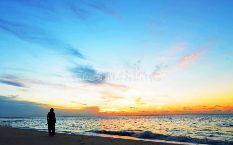 Silhouetvrouw, zonsondergang op het oceaanstrand van het Vriendschappunt, het Eiland van het Noordenstradbroke, Australië stock afbeelding