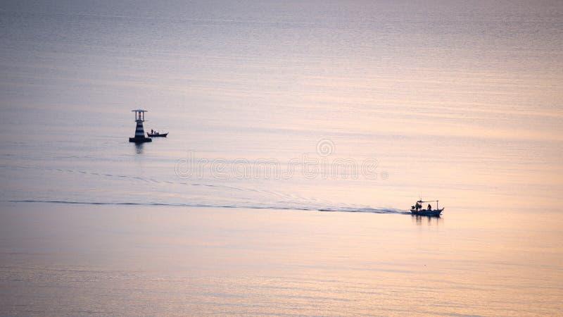 Silhouetzonsopgang van het zeil van de visserijboot op kalme overzees met lightho stock fotografie
