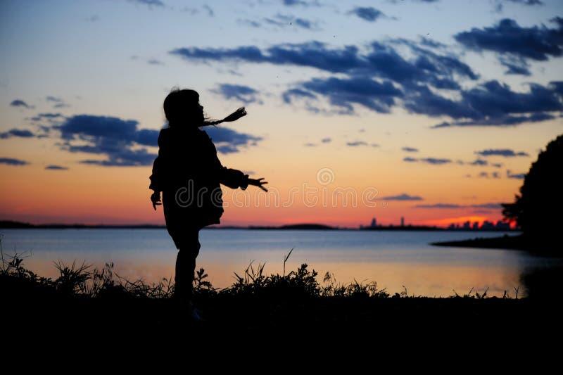 Silhouhette eines Kindmädchens, das in den Sonnenuntergang geht stockfotografie