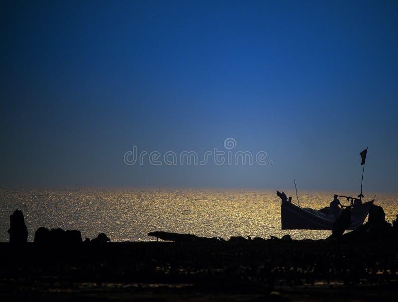 Silhoutte της ενιαίας βάρκας στη θάλασσα κατά τη διάρκεια του ηλιοβασιλέματος στοκ εικόνα με δικαίωμα ελεύθερης χρήσης