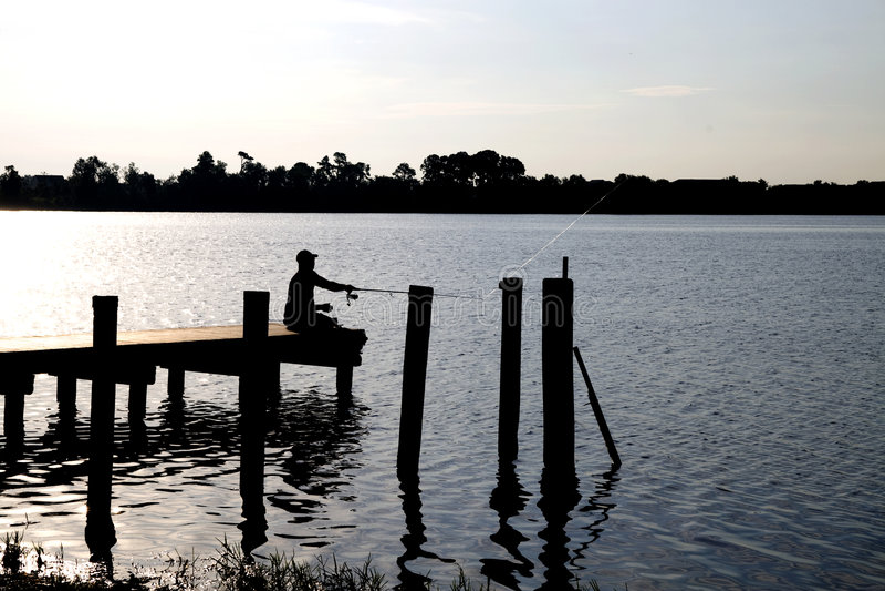Silhoutte del pescador en muelle foto de archivo