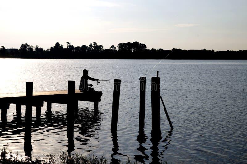 Silhoutte del pescatore sul bacino fotografia stock