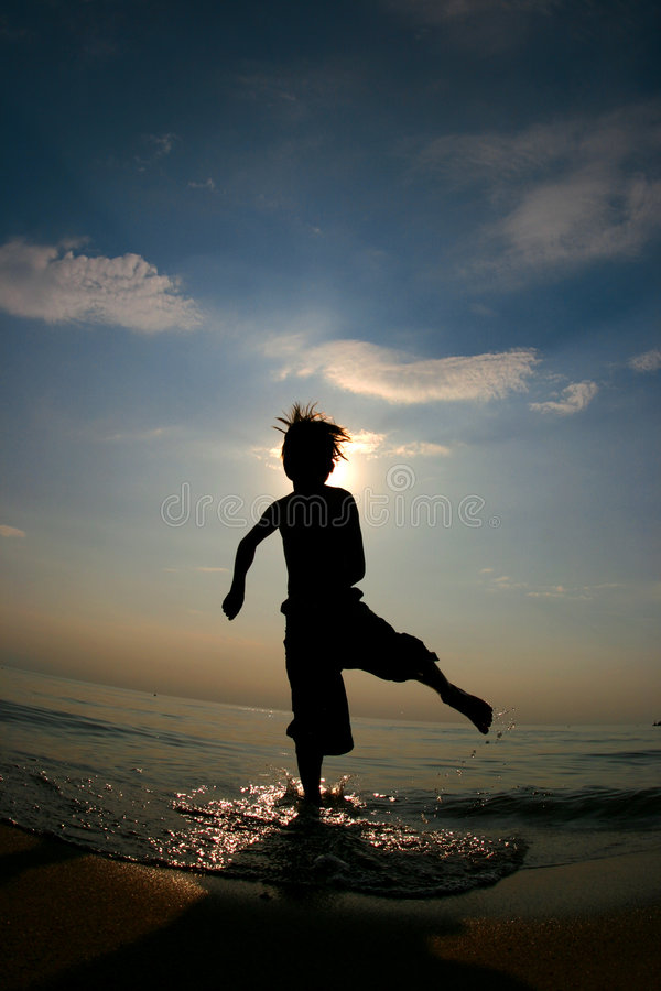 Silhoutte del ragazzo che gioca in acqua ad una spiaggia fotografia stock libera da diritti