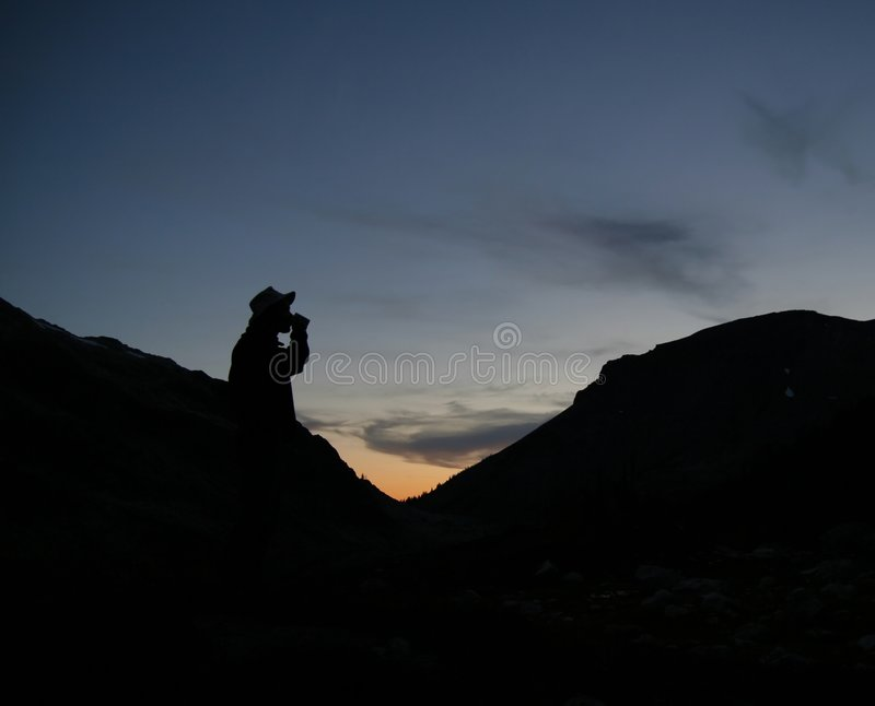 Silhoutte Do Caminhante Que Bebe Da Caneca Nas Montanhas Imagem de Stock Royalty Free