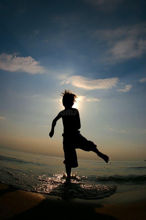 Silhoutte do menino que joga na água em uma praia fotografia de stock royalty free