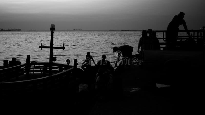 Silhoutte do trabalho do pescador no porto imagens de stock