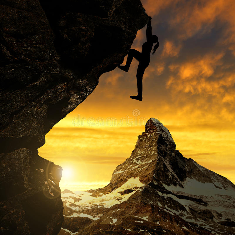 Silhoutte of girl climbing on rock at sunset stock photo