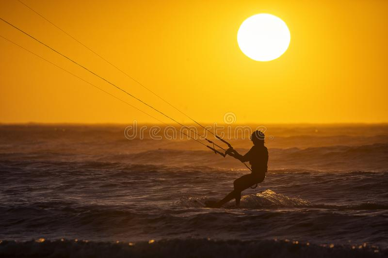 Silhoutte of kitesurfers enjoying big waves at sunset in Essaouira, Morocco. Beautiful landscape in background.  stock photos