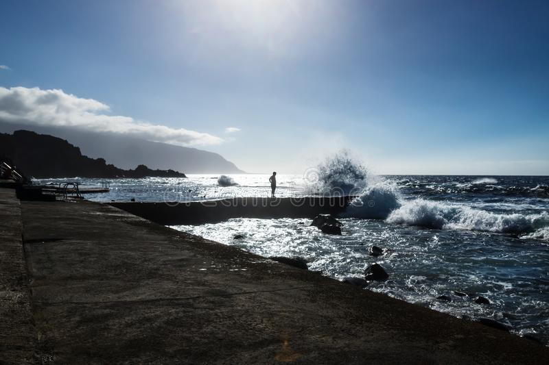 Silhoutte of a man in a natural ocean pool with a huge splash at Frontera, El Golfo, El Hierro, Canary Islands, Spain royalty free stock images