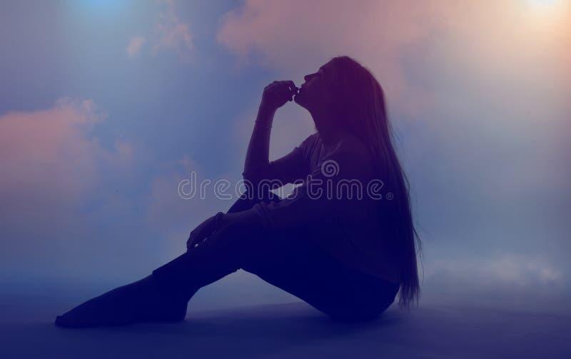 Silhoutte stående av en ung härlig kvinna som är avslappnande och drömma med himmelbakgrund arkivfoton