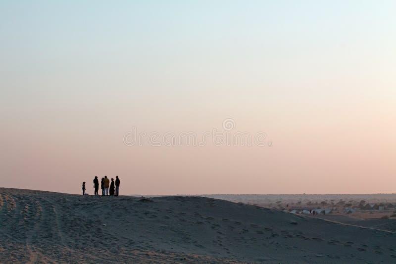 Silhoutted人小组和孩子沙子沙丘的在黄昏 库存照片