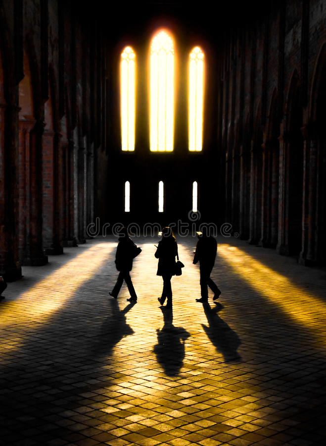 Silhouttes av tre personer som går till och med solljus i en kloster arkivbilder