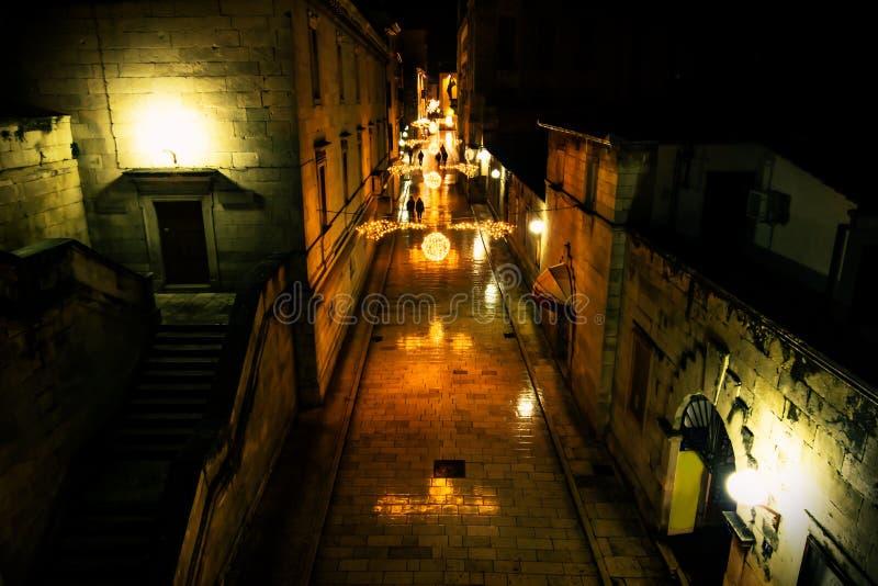 Silhouttes die langs de verfraaide komst lopen cobbled straten van Zadar bij nacht, Kroatië stock foto's