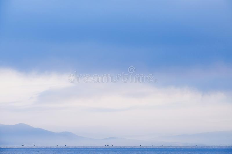 Silhouttes of fisher boats in the early morning mist on Lake Ohrid, Albania royalty free stock images