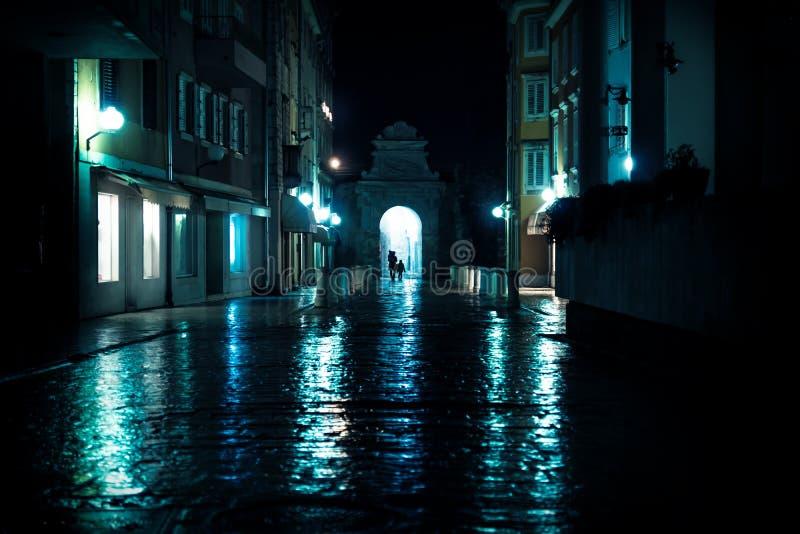 Silhouttes som går till och med båge på våta lappade gator i Zadar, Kroatien arkivfoto