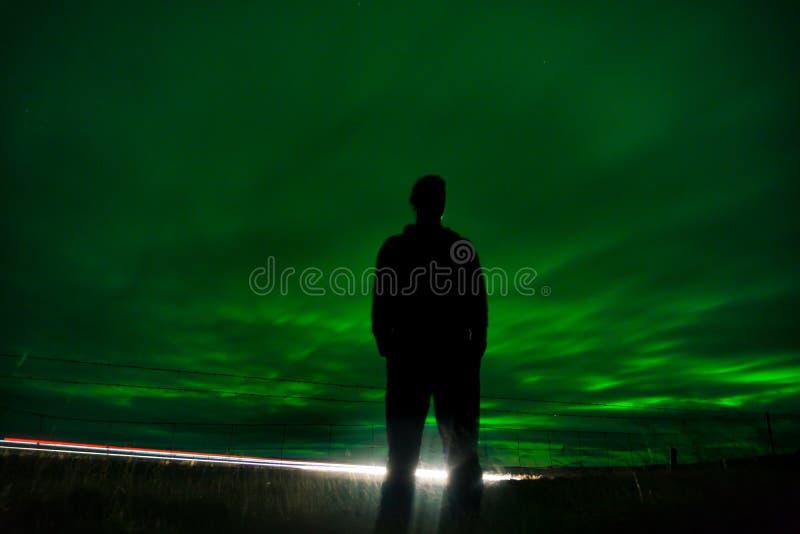 Silhueta épico por um homem na frente da aurora boreal quando a imagem de stock