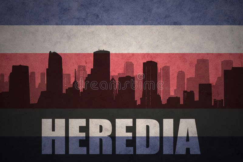 Silhueta abstrata da cidade com texto Heredia na bandeira rican da costela do vintage ilustração royalty free
