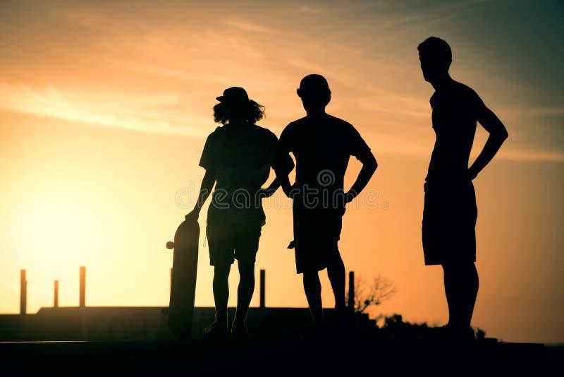 Silhueta adolescente dos meninos no parque do patim no verão imagens de stock royalty free