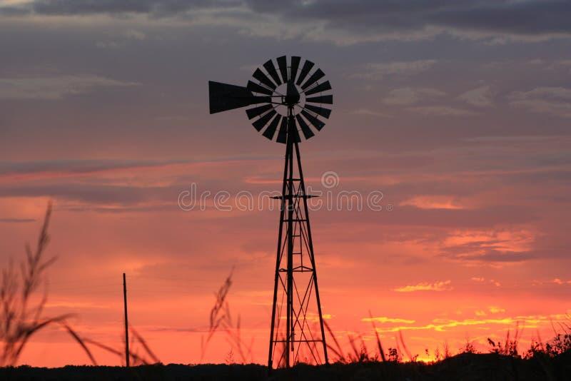 Silhueta alaranjada do moinho de vento do céu de Kansas imagens de stock