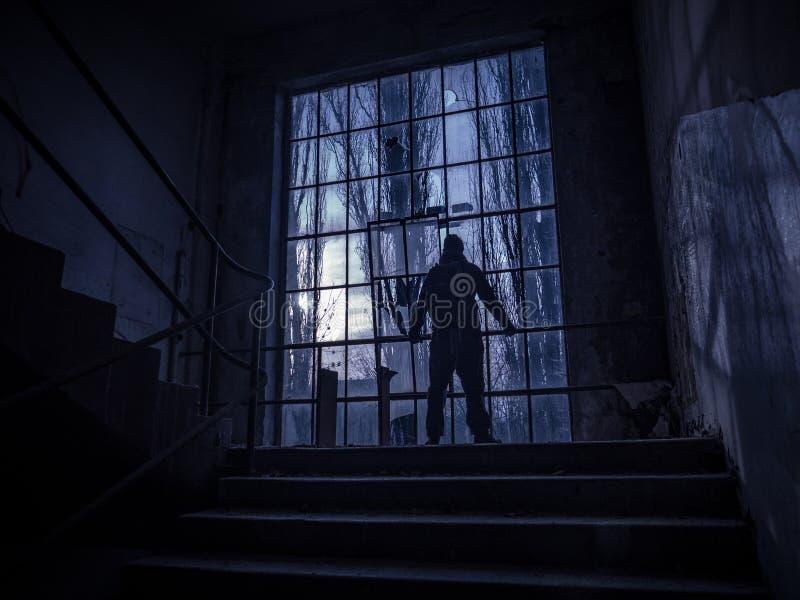 Silhueta assustador do homem do baixo sol através das janelas fotos de stock royalty free