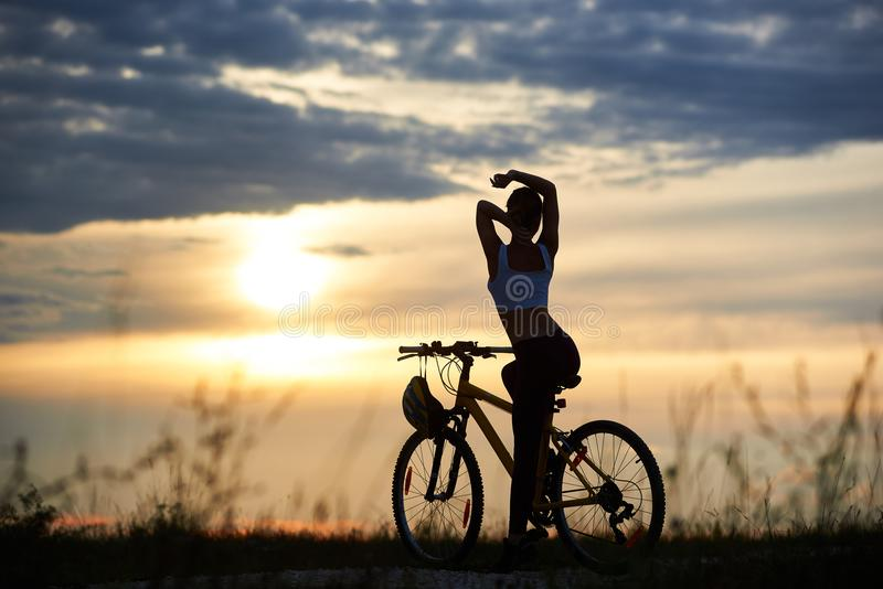 Silhueta bonita da vista traseira da fêmea perfeita do corpo contra o céu da noite do fundo com sol de ajuste foto de stock