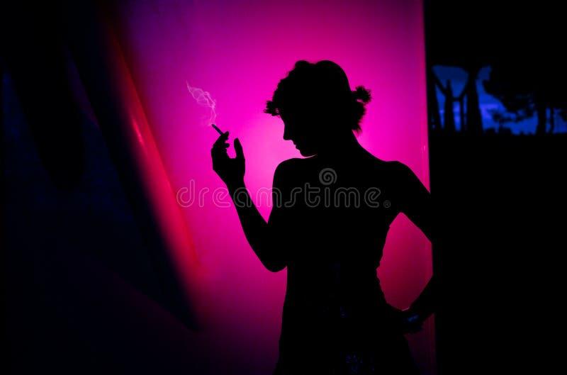 Silhueta bonita de fumo da mulher no fundo cor-de-rosa lifestyle fotos de stock royalty free