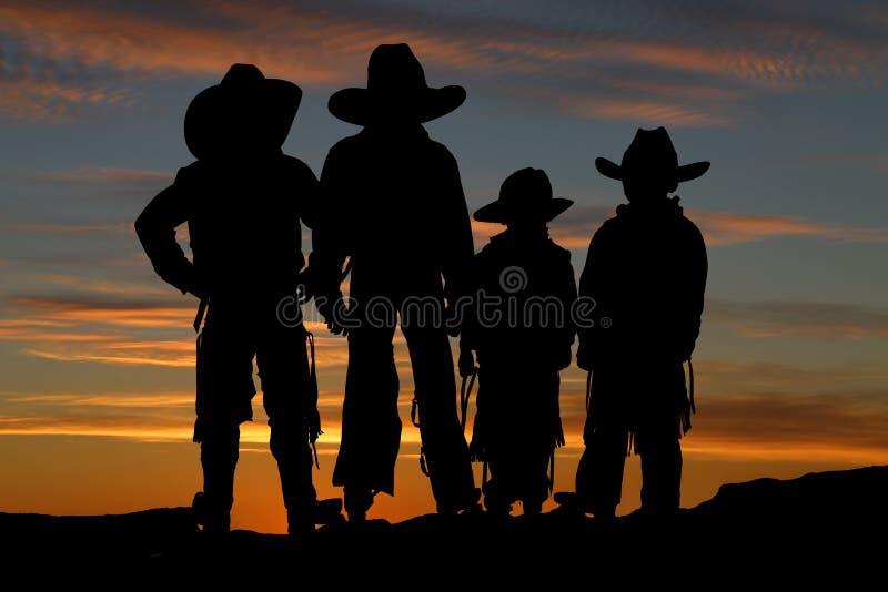 Silhueta bonita de quatro vaqueiros novos com um backgro do por do sol imagem de stock
