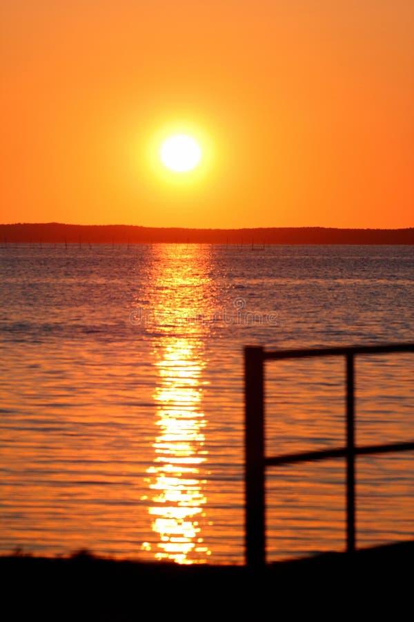 Silhueta borrada de uma cerca em um litoral durante o por do sol fotos de stock royalty free