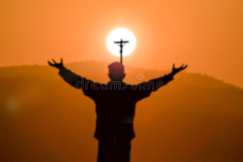 Silhueta borrada do homem que reza a cruz na montanha no tempo do por do sol foto de stock