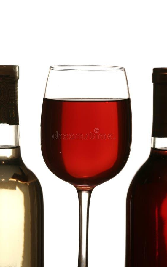 Silhueta colorida do vidro de um vinho vermelho entre o frasco de vinho dois fotografia de stock royalty free