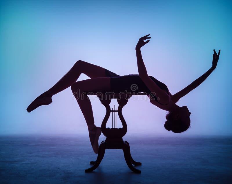 A silhueta da bailarina nova no de madeira foto de stock royalty free