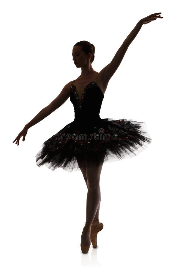 Silhueta da bailarina que faz o arabesque da posição de bailado contra o fundo branco fotografia de stock