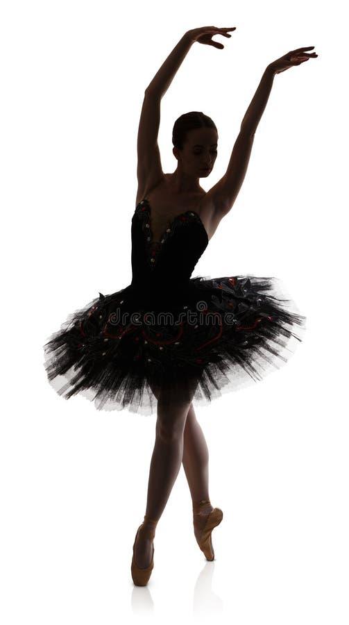 Silhueta da bailarina que faz o arabesque da posição de bailado contra o fundo branco fotos de stock royalty free