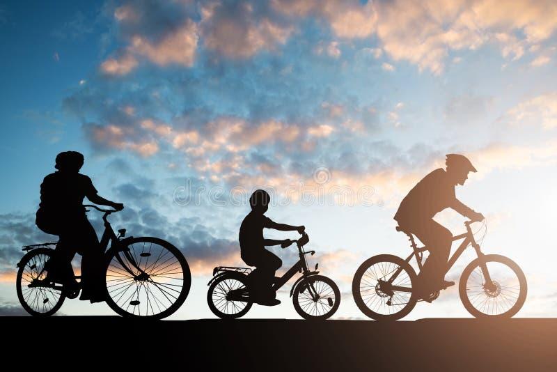 Silhueta da bicicleta da equita??o da fam?lia fotografia de stock