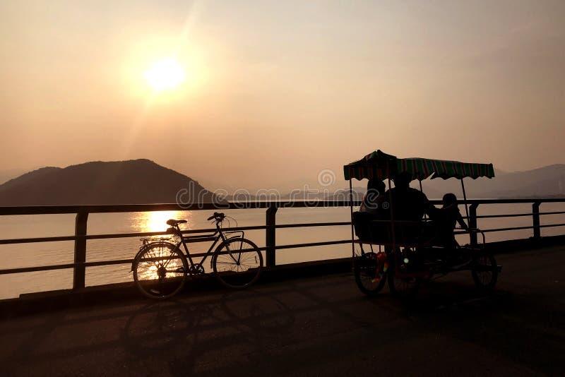 Silhueta da bicicleta retro, bicicleta da família, cerca, oceano, montanha imagens de stock royalty free