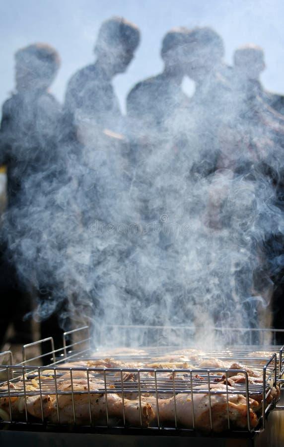 Silhueta da carne de espera do assado da galinha dos povos no fumo imagens de stock