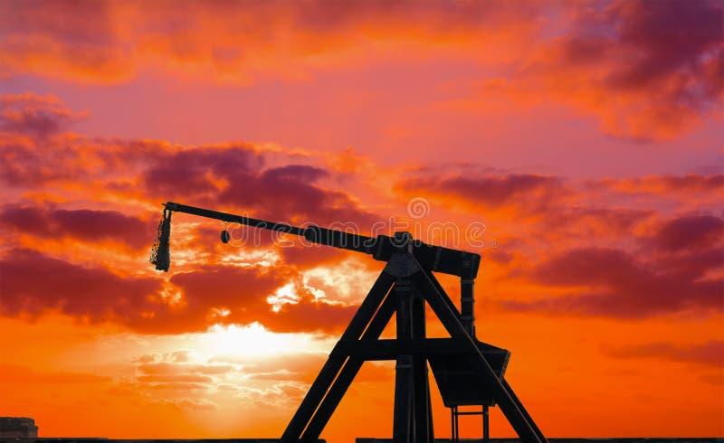 Silhueta da catapulta sob um por do sol vermelho fotografia de stock