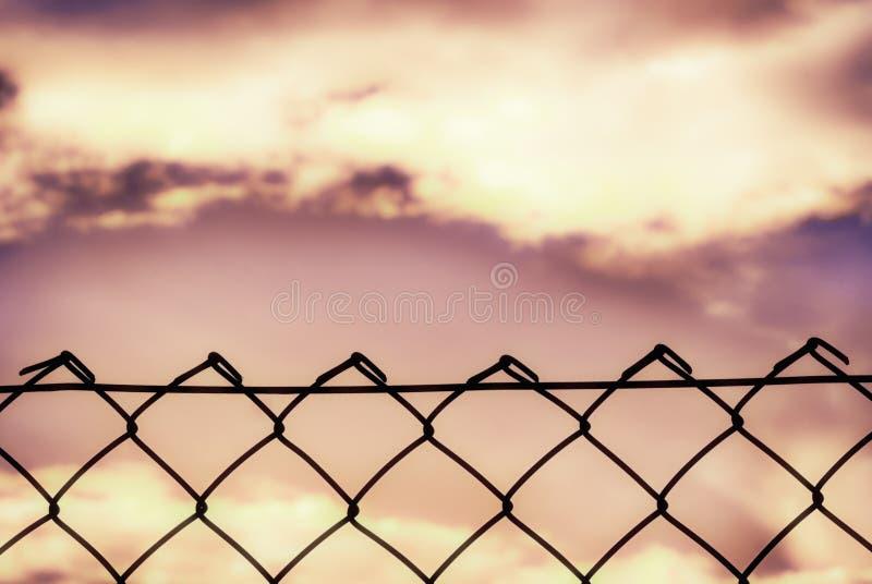 Silhueta da cerca no preto sob um c?u vibrante imagens de stock