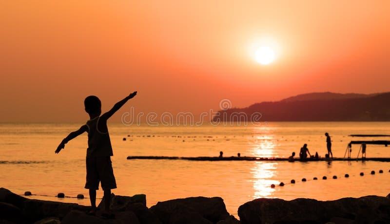 A silhueta da criança de encontro ao por do sol alaranjado foto de stock