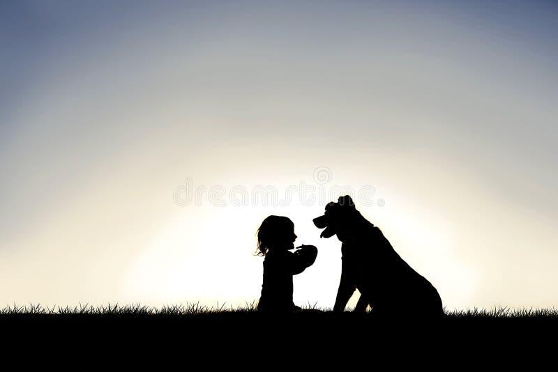 Silhueta da criança pequena doce que senta-se fora com seu Loyal Family Pet Dog fotos de stock