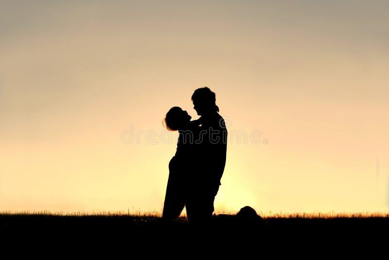 Silhueta da criança que ri e que abraça o pai no por do sol fotos de stock