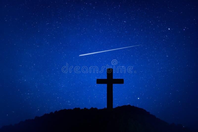 Silhueta da cruz do crucifixo na montanha na noite com fundo da estrela e do espaço imagem de stock