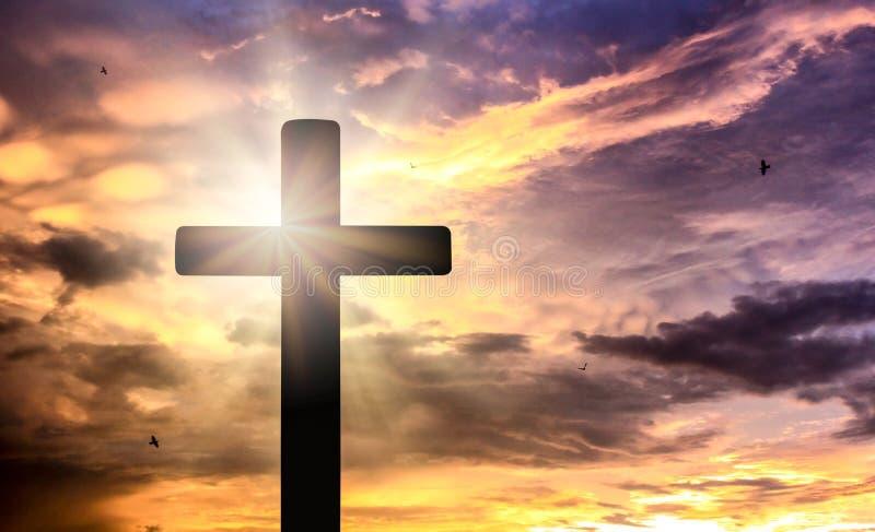 Silhueta da cruz do crucifixo no tempo do por do sol com fundo santamente e claro foto de stock