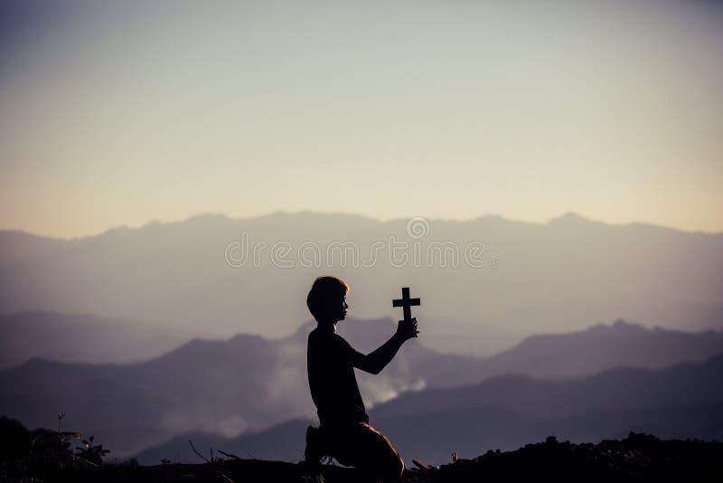 A silhueta da cruz humana da terra arrendada da m?o, o fundo ? o nascer do sol , Conceito para o cristão, cristandade, religião c imagem de stock royalty free