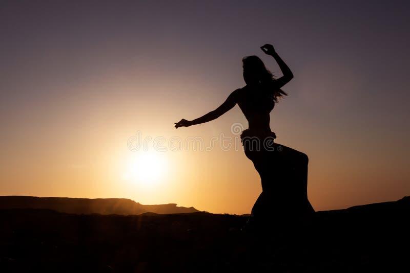 Silhueta da dança da mulher à dança do ventre famosa com por do sol no deserto de Namibe com gargantas África angola foto de stock