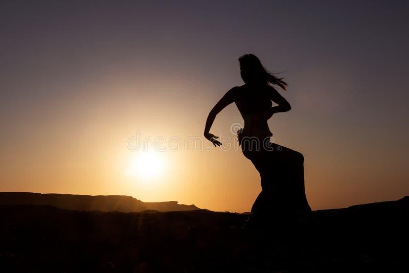 Silhueta da dança da mulher à dança do ventre famosa com por do sol no deserto de Namibe com gargantas África angola fotos de stock royalty free