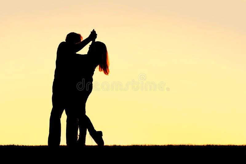 Silhueta da dança nova feliz dos pares no por do sol imagem de stock