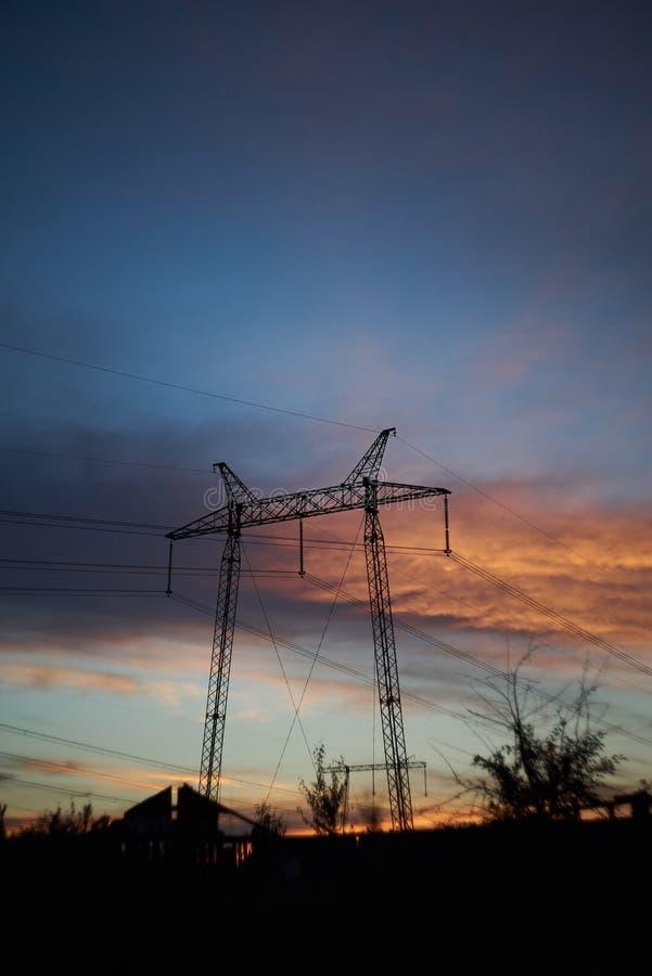 Silhueta da estrutura elétrica de alta tensão do polo cabos distribuidores de corrente na torre de poder grande imagem de stock royalty free