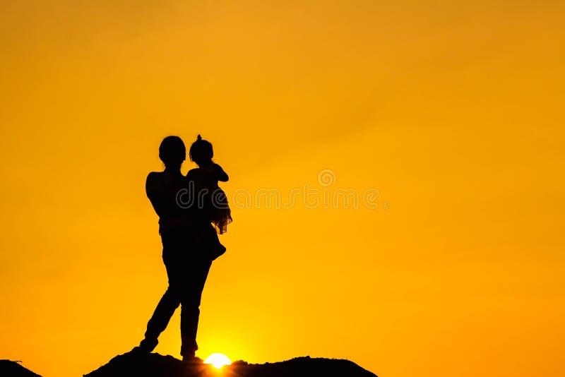 A silhueta da família de estar da mãe e da criança olha o por do sol e o céu na laranja na noite imagem de stock